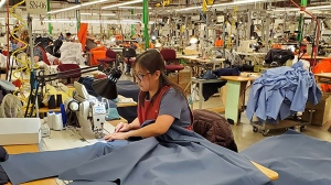 A worker at WearWell Garments Ltd. in Stellarton cuts out fabric for medical gowns. (Source: Facebook/WearWell Garments Ltd.)
