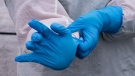 A nurse slips on protective gloves at a drive-through clinic at Ste-Justine Children Hospital in Montreal, on Wednesday, April 1, 2020. The Quebec government has expressed concerns for the diminishing supplies of personal protective equipment. THE CANADIAN PRESS/Paul Chiasson