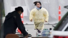 A health care worker runs through the parking lot of a COVID-19 testing area in Burnaby, B.C. Wednesday, April 1, 2020. THE CANADIAN PRESS/Jonathan Hayward