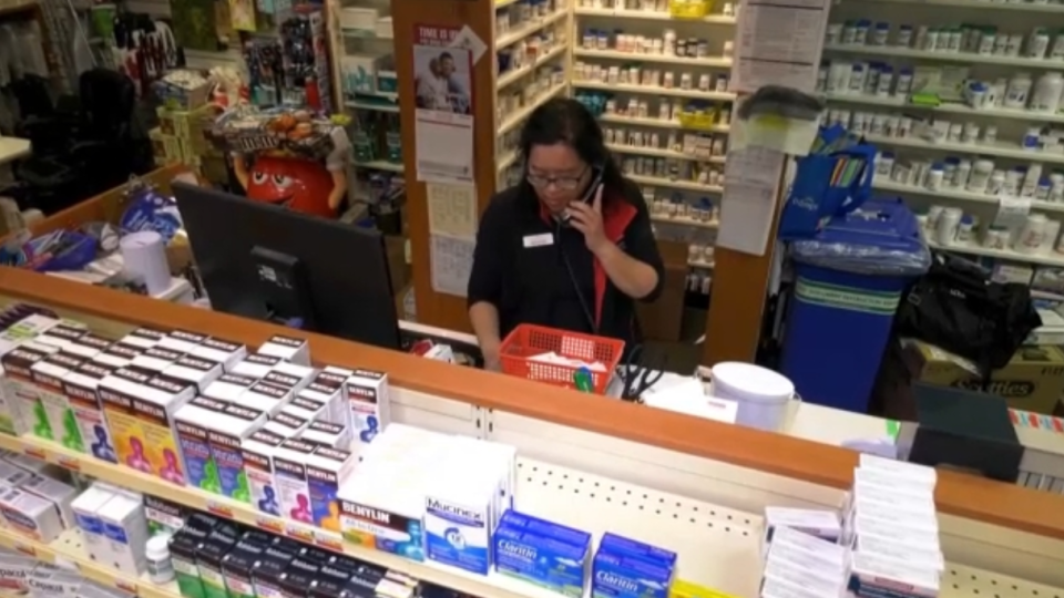 Pharmacy manager Mona Kwong works behind the counter at the Pharmasave on Howe Street in downtown Vancouver on April 1, 2020.
