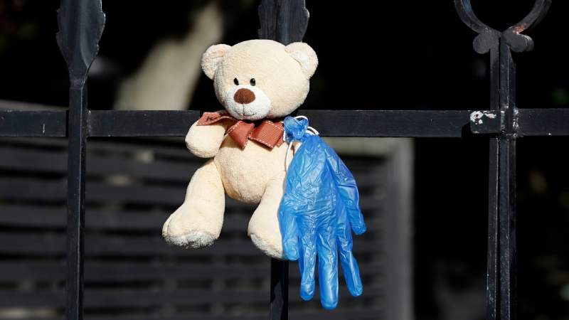 In this Tuesday, March 31, 2020 photo, a teddy bear hangs on a fence outside a house in Christchurch, New Zealand. New Zealanders are embracing an international movement in which people are placing teddy bears in their windows during coronavirus lockdowns to brighten the mood and give children a game to play by spotting the bears in their neighborhoods. (AP Photo/Mark Baker)