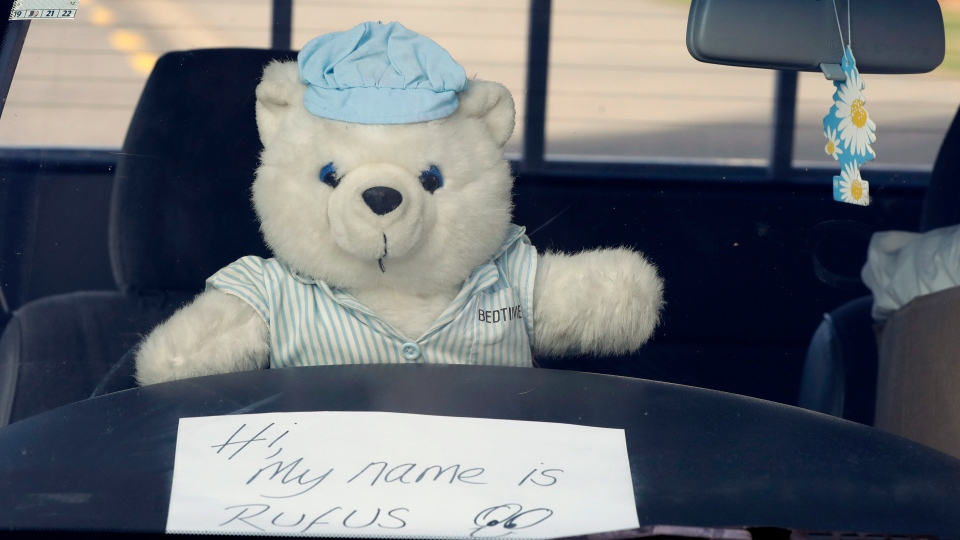 In this Tuesday, March 31, 2020, photo, a teddy bear sits on a the wheel of a car outside a house in Christchurch, New Zealand. New Zealanders are embracing an international movement in which people are placing teddy bears in their windows during coronavirus lockdowns to brighten the mood and give children a game to play by spotting the bears in their neighborhoods. (AP Photo/Mark Baker)
