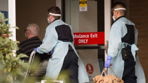 British Columbia Ambulance Service paramedics transfer a patient to the Lions Gate Hospital in North Vancouver, B.C. Tuesday, March 31, 2020. THE CANADIAN PRESS/Jonathan Hayward