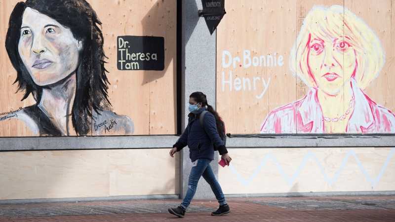A woman wearing a protective face mask walks past portraits of Dr. Theresa Tam and Dr. Bonnie Henry on a boarded up business in downtown Vancouver, B.C. Wednesday, April 1, 2020. THE CANADIAN PRESS/Jonathan Hayward