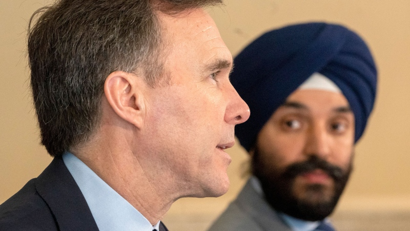 Federal Finance Minister Bill Morneau speaks as Minister of Innovation, Science and Industry Navdeep Bains listens at a news conference in Toronto on Wednesday April 1, 2020. THE CANADIAN PRESS/Frank Gunn