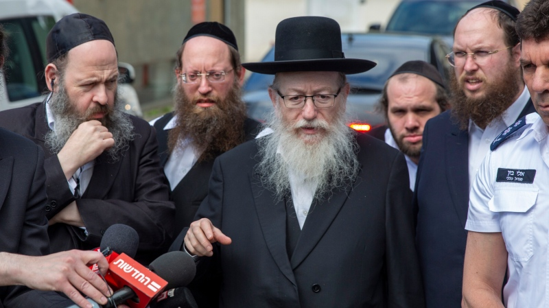 In this Monday, March 2, 2020 photo, Israel's Health Minister Yaakov Litzman delivers a statement as he visits a makeshift tent for quarantined coronavirus voters in Tel Aviv, Israel. (AP Photo/Ariel Schalit)