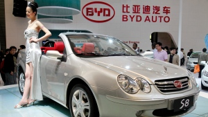 In this April 23, 2009 file photo, a model poses next to Chinese auto maker BYD's S8 Convertible at the Shanghai International Auto Show in Shanghai, China. (AP Photo/Eugene Hoshiko, File)