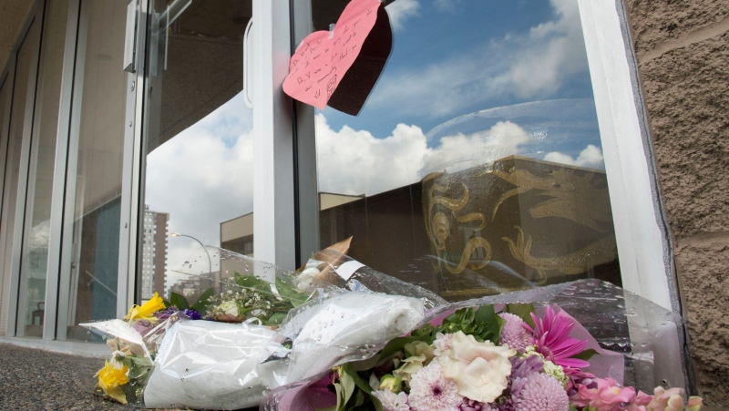 Flowers are seen at the front door of Dr. Denis Vincent's dental practice in North Vancouver, B.C. Tuesday, March 31, 2020. Dr. Denis Vincent is being remembered as a dedicated dentist who made patient care and safety his top priority. Vincent was 64 when he died on March 22 after attending the Pacific Dental Conference, which drew about 15,000 people. THE CANADIAN PRESS/Jonathan Hayward