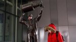 A pedestrian walks past a Wayne Gretzky statue sporting a mask outside Rogers place during the COVID-19 pandemic, in Edmonton, Thursday, March 26, 2020. THE CANADIAN PRESS/Jason Franson
