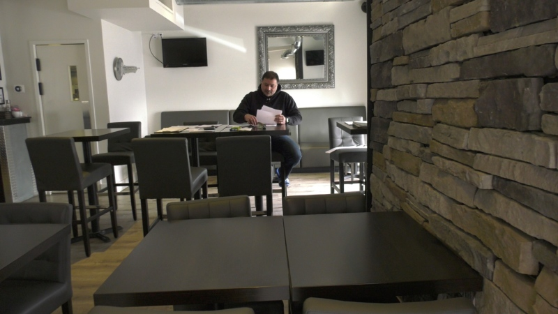 Owner Talaal Baroudi of The Vault Restaurant in Manotick is looking over bills. April 02, 2020. (Tyler Fleming / CTV News Ottawa)