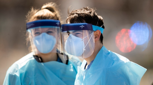 Medical workers in protective masks wait to administer COVID-19 tests at a facility in Camden, N.J., Wednesday, April 1, 2020. The new coronavirus causes mild or moderate symptoms for most people, but for some, especially older adults and people with existing health problems, it can cause more severe illness or death.(AP Photo/Matt Rourke)