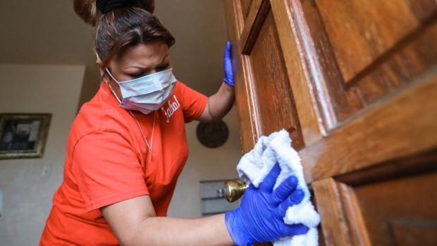 Woman wipes down doorknob. (Nathan J, Fish / The Las Cruces Sun News via AP)
