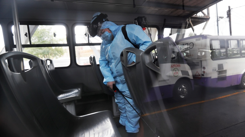 A member of cleaning crew wearing protective mask and suit disinfects a bus as a preventive measure against the spread of the new coronavirus, in Mexico City, Thursday, April 2, 2020. (AP Photo/Marco Ugarte)