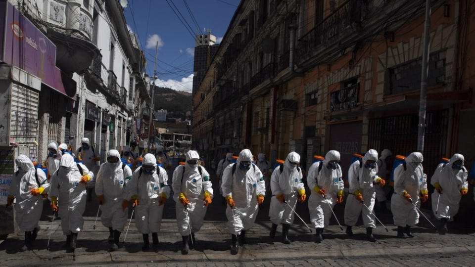 City workers fumigate a street to help contain the spread of the new coronavirus in La Paz, Bolivia, Thursday, April 2, 2020. (AP Photo/Juan Karita)