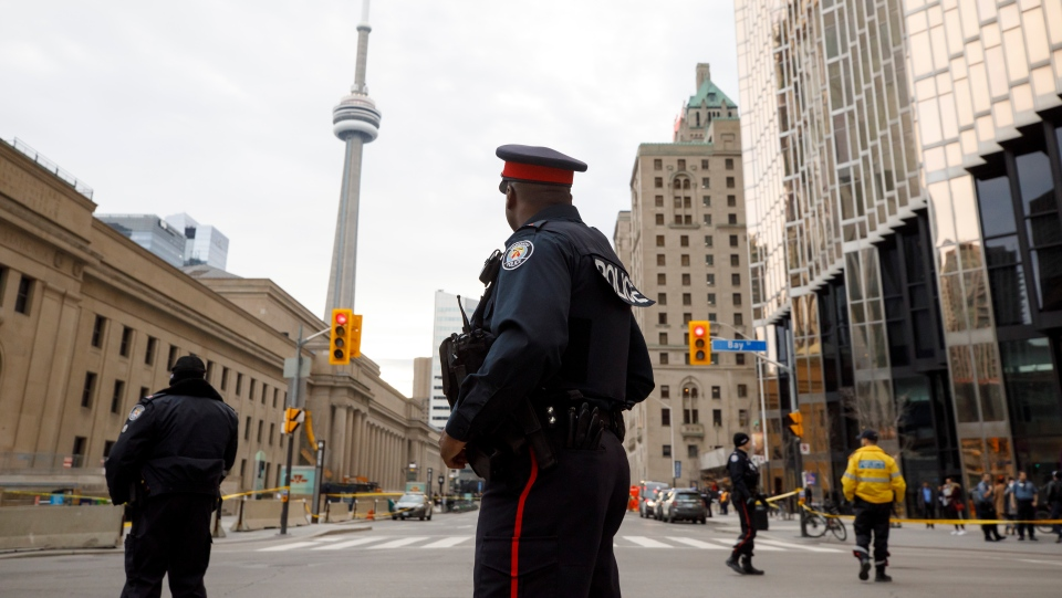 FILE - Toronto Police officers work an active crime scene in downtown Toronto in this file photo from Monday, March 9, 2020. THE CANADIAN PRESS/Cole Burston