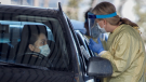 Alberta Health Services employees speak with a drivers at a drive-thru testing facility in Calgary, Alta., Friday, March 27, 2020, amid a worldwide COVID-19 flu pandemic. THE CANADIAN PRESS/Jeff McIntosh​