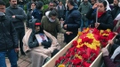 Mourners gather around the open coffin of Helin Bolek, a member of a popular folk music group that is banned in Turkey, during the funeral procession in Istanbul, Friday, April 3, 2020. (Ibrahim Mase/DHA via AP)