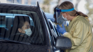 Alberta Health Services employees speak with a drivers at a drive-thru testing facility in Calgary, Alta., Friday, March 27, 2020, amid a worldwide COVID-19 flu pandemic. THE CANADIAN PRESS/Jeff McIntosh
