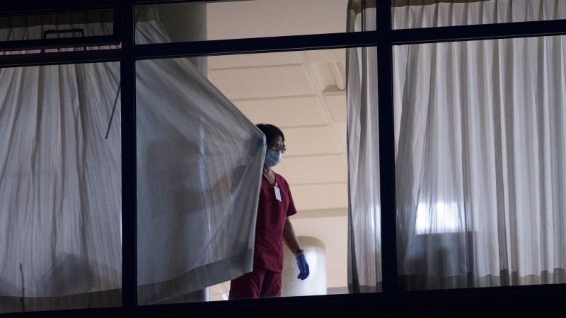 A worker is seen closing the curtains at the Lynn Valley Care Centre in North Vancouver, B.C., Wednesday, March 25, 2020. THE CANADIAN PRESS/Jonathan Hayward