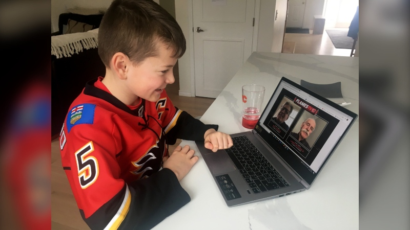 Lucas Fursier watches a video sent to him by Calgary Flames alumni Lanny McDonald and Mike Vernon. (Photo courtesy Amanda Fursier)