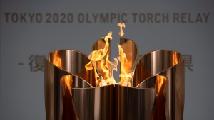 In this March 24, 2020, file photo, the Olympic Flame burns during a ceremony in Fukushima City, Japan. Tokyo's governor is considering the possibility of using the unfinished Olympic Athletes Village as a temporary hospital for coronavirus infected patients. The massive village on Tokyo Bay could house up to 18,000 people during the Olympics. (AP Photo/Jae C. Hong, File)