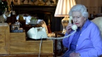 In this photo made available by Buckingham Palace, Britain's Queen Elizabeth II speaks to Prime Minister Boris Johnson from Windsor Castle, Windsor, England, Wednesday March 25, 2020, for her weekly audience. Prince Charles, the heir to the British throne, has tested positive for the new coronavirus, royal officials confirmed Wednesday. Buckingham Palace said Queen Elizabeth II, 93, remains at her Windsor Castle home west of London with her 98-year-old husband, Prince Philip. (Buckingham Palace via AP)