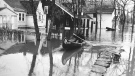 An image of man canoeing in a flooded residential area in 1950. (Source: Province of Manitoba)