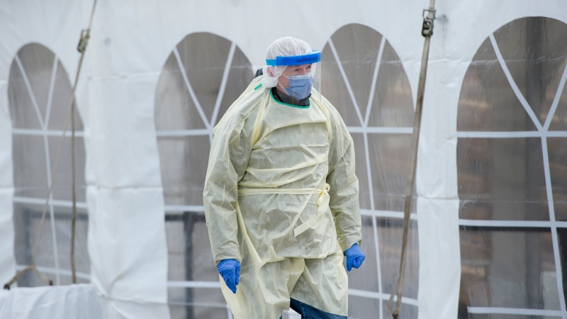 A health care worker wearing protective gear walks between a COVID-19 assessment centre at The Scarborough Hospital in Scarborough, Ont., on Friday, April 3, 2020. Health officials and the government has asks that people stay inside to help curb the spread of COVID-19. THE CANADIAN PRESS/Nathan Denette