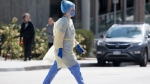 A healthcare worker is seen wearing full personal protection equipment crosses the street outside the Royal Columbian Hospital in New Westminster, B.C. Friday, April 3, 2020. THE CANADIAN PRESS/Jonathan Hayward