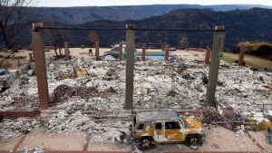 In this Dec. 3, 2018, file photo, a vehicle rests in front of a home leveled by the Camp Fire in Paradise, Calif. California power regulators are weighing a recommendation to back off plans to fine Pacific Gas and Electric an additional $462 million for igniting a series of Northern California 2018 deadly wildfires rather than risk that the harsher punishment will scuttle the utility's plan to emerge from bankruptcy protection, the state's Public Utilities Commission said in a document made public Monday, March 30, 2020. (AP Photo/Noah Berger, File)