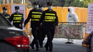 Chinese police officers march past a checkpoint around the Wuhan Central Hospital in Wuhan in central China's Hubei province Saturday, April 4, 2020. (AP Photo/Ng Han Guan)
