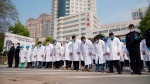 In this photo released by China's Xinhua News Agency, medical workers bow their heads during a national moment of mourning for victims of coronavirus in Wuhan in central China's Hubei Province, Saturday, April 4, 2020. (Cai Yang/Xinhua via AP)