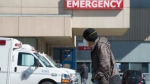 A man wears a protective face mask as he walks past the emergency department of the Royal Columbian Hospital in New Westminster, B.C. Friday, April 3, 2020. THE CANADIAN PRESS/Jonathan Hayward