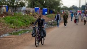 A man wearing a face mask to protect against coronavirus, cycles on the street in Thokoza, east of Johannesburg, South Africa, Friday, April 3, 2020. (AP Photo/Themba Hadebe)