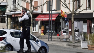 A police officer gives a phone call after a man wielding a knife attacked residents venturing out to shop in the town under lockdown, Saturday April 4, 2020 in Romans-sur-Isere, southern France. The alleged attacker was arrested by police nearby, shortly after the attack. Prosecutors did not identify him. They said he had no documents but claimed to be Sudanese and to have been born in 1987. (AP Photo)