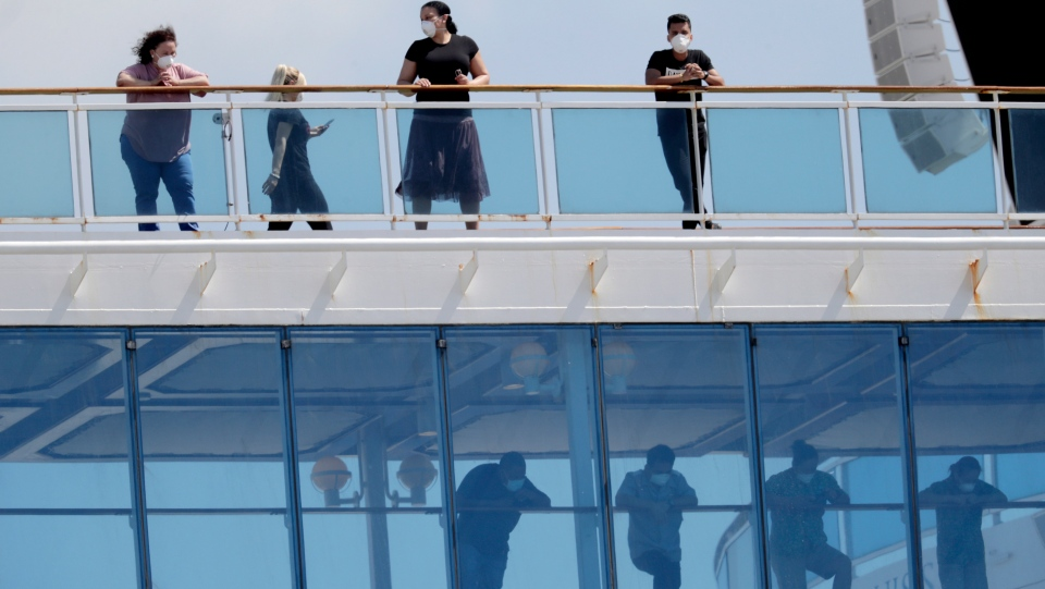 People wearing protective masks look out from the Coral Princess cruise ship while docked at PortMiami during the new coronavirus outbreak, Saturday, April 4, 2020, in Miami. (AP Photo/Lynne Sladky)
