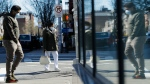 Pedestrians wearing personal protective equipment walk along Broadway, Saturday, April 4, 2020, in the Queens borough of New York. (AP Photo/Frank Franklin II)