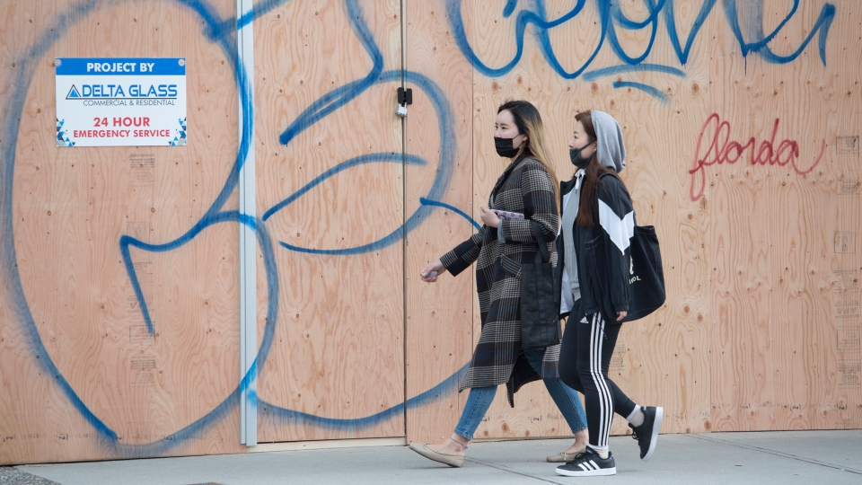 Two women wearing protective face masks make their way past a boarded up Banana Republic store in downtown Vancouver Monday, March 30, 2020. Several stores that have shut down due to COVID-19 have been emptying the contents out of the premises along with boarding up the windows. (THE CANADIAN PRESS / Jonathan Hayward)