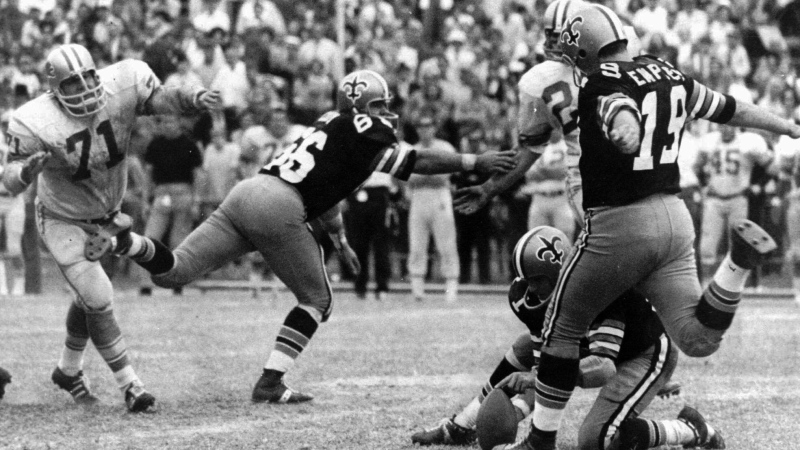 In this Nov. 8, 1970, file photo, New Orleans Saints' Tom Dempsey (19) moves up to kick a 63-yard field goal as teammate Joe Scarpati holds the ball and Detroit Lions' Alex Karras (71) rushes in while Saints' Bill Cody (66) blocks, in New Orleans. Dempsey, who played in the NFL despite being born without toes on his kicking foot and made a record 63-yard field goal, died late Saturday, April 4, 2020, in New Orleans while struggling with complications from the new coronavirus, his daughter said. He was 73 years old. (AP Photo/File)