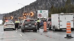 Police forces check on motorists as highway 175 is closed, Sunday, March 29, 2020 north of Quebec City. THE CANADIAN PRESS/Jacques Boissinot