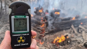 A Geiger counter shows increased radiation level against the background of the forest fire burning near the village of Volodymyrivka in the exclusion zone around the Chernobyl nuclear power plant, Ukraine, Sunday, April 5, 2020. (AP Photo/Yaroslav Yemelianenko)