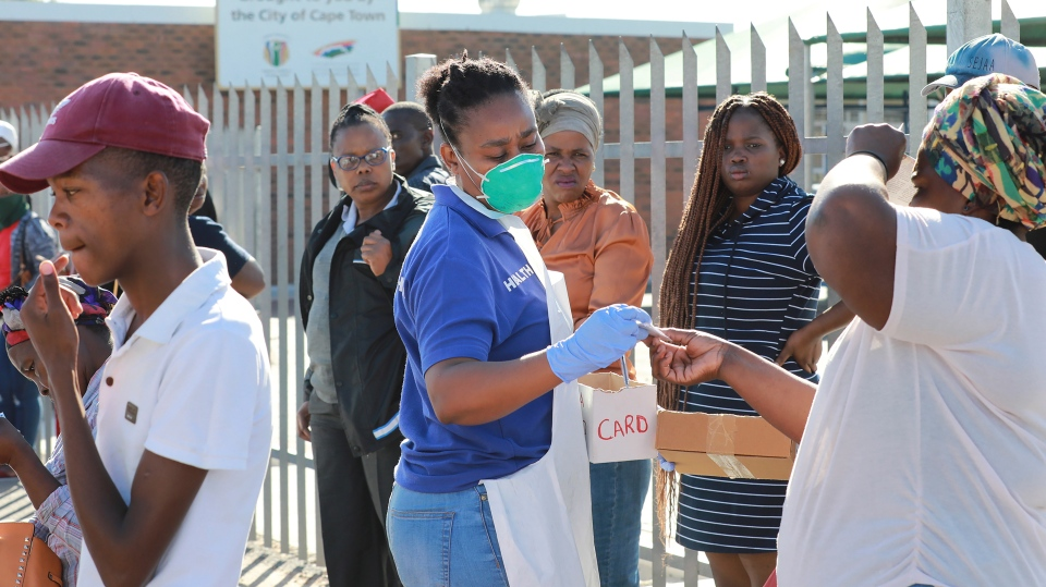 In this photo taken Thursday, April 2, 2020 medical workers prepare to test people for COVID-19 at a testing clinic in Khayelitsha, Cape Town, South Africa. (AP Photo/Nardus Engelbrecht)