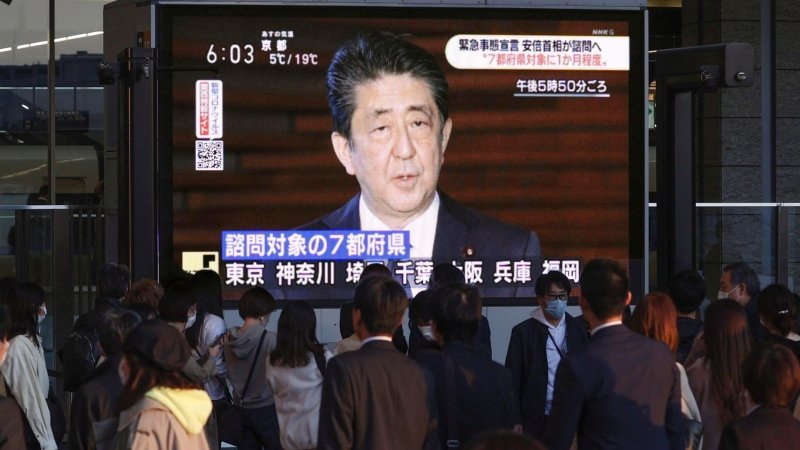 People watch TV screen showing that Japanese Prime Minister Shinzo Abe speaks at the prime minister official residence, in Osaka, Japan, Monday, April 6, 2020. Abe said that he will declare a state of emergency for Tokyo and six other prefectures as early as Tuesday to bolster measures to fight the coronavirus outbreak, but that there will be no hard lockdowns. (Kyodo News via AP)
