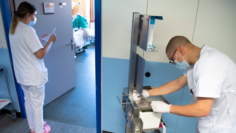 Swiss army soldier Arthur, right, helps medical worker by disinfecting a medical trolley in the coronavirus and COVID-19 unit at the HiB Hospital (Hopital intercantonal de la Broye) in Payerne, Switzerland, Monday, April 6, 2020. (Laurent Gillieron/Pool/Keystone via AP)