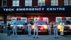 Health-care workers at St. Paul's Hospital acknowledge applause and cheers from people outside the hospital as a convoy of first responders with lights and sirens on parade past to show support for the hospital staff, in Vancouver, on Sunday, April 5, 2020. (Darryl Dyck / The Canadian Press)