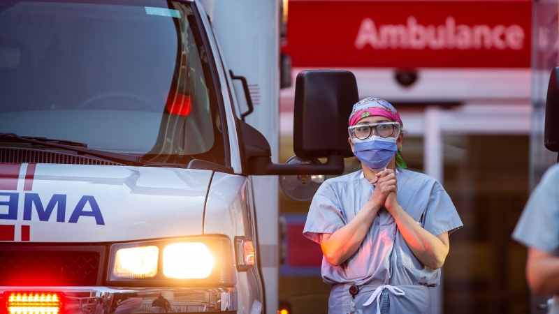 A health-care worker at St. Paul's Hospital acknowledges applause and cheers from people outside the hospital as a convoy of first responders with lights and sirens on parade past to show support for the hospital staff, in Vancouver, on Sunday, April 5, 2020. (Darryl Dyck / The Canadian Press)