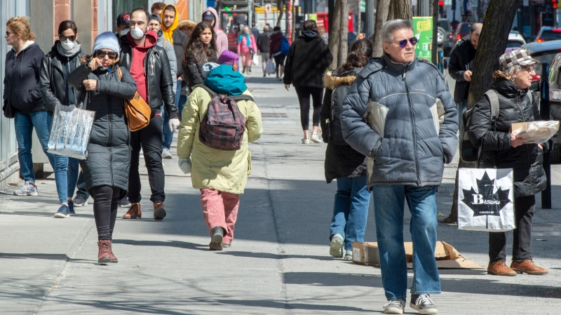 Pedestrians walk down St. Catherine Street Monday April 6, 2020 in Montreal. (THE CANADIAN PRESS / Ryan Remiorz)