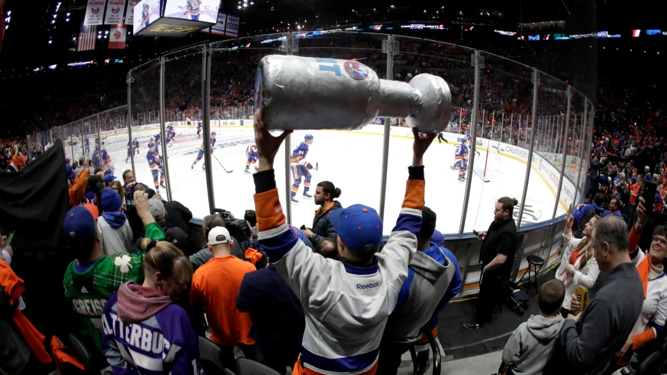 In this April 10, 2019, file photo, New York Islanders players take the ice as a man holds a makeshift Stanley Cup prior to Game 1 of an NHL hockey first-round playoff series against the Pittsburgh Penguins in Uniondale, N.Y. (AP Photo/Julio Cortez, FIle)
