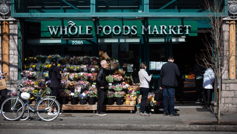 People maintain distance between one another while waiting in line to enter a Whole Foods Market grocery store as the store limits the number of customers permitted inside due to concerns about the spread of COVID-19. THE CANADIAN PRESS/Darryl Dyck