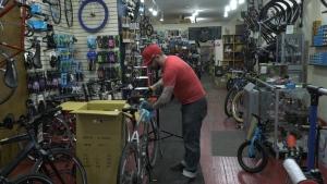 Joe Mamma Cycles owner Jose Bray sanitizes a bike before repairs. Ottawa, ON. April 6, 2020. (Tyler Fleming / CTV News Ottawa)